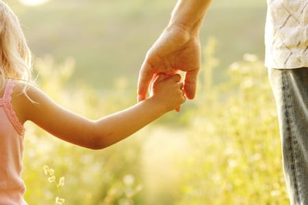 35489272 - a parent holds the hand of a small child